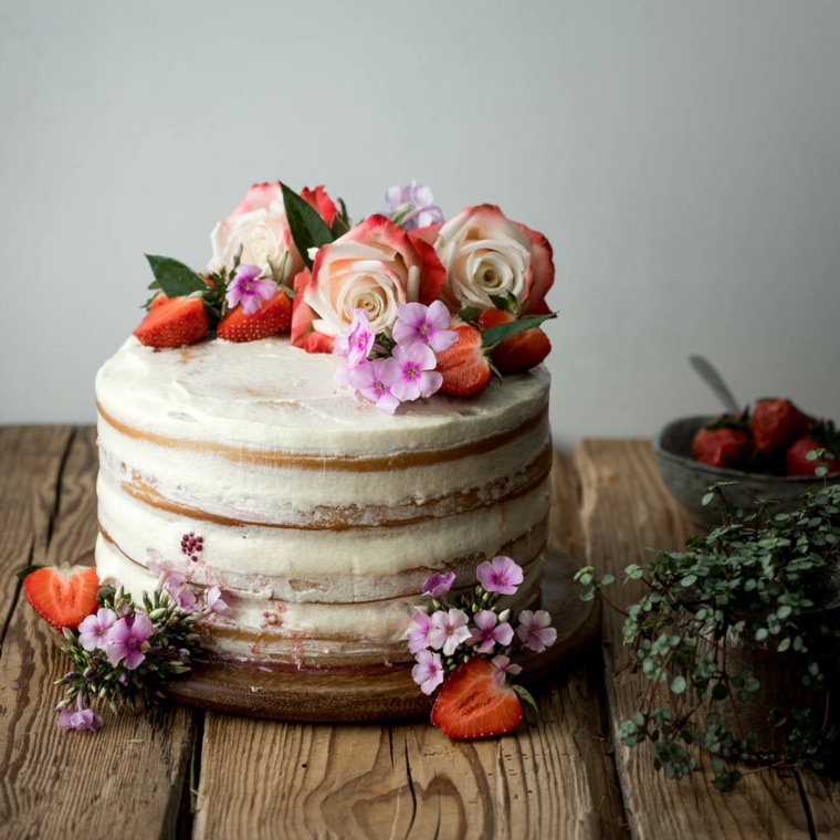 Torta compleanno bimba, dolce a strati con crema, decorazioni torta con fragole e fiori