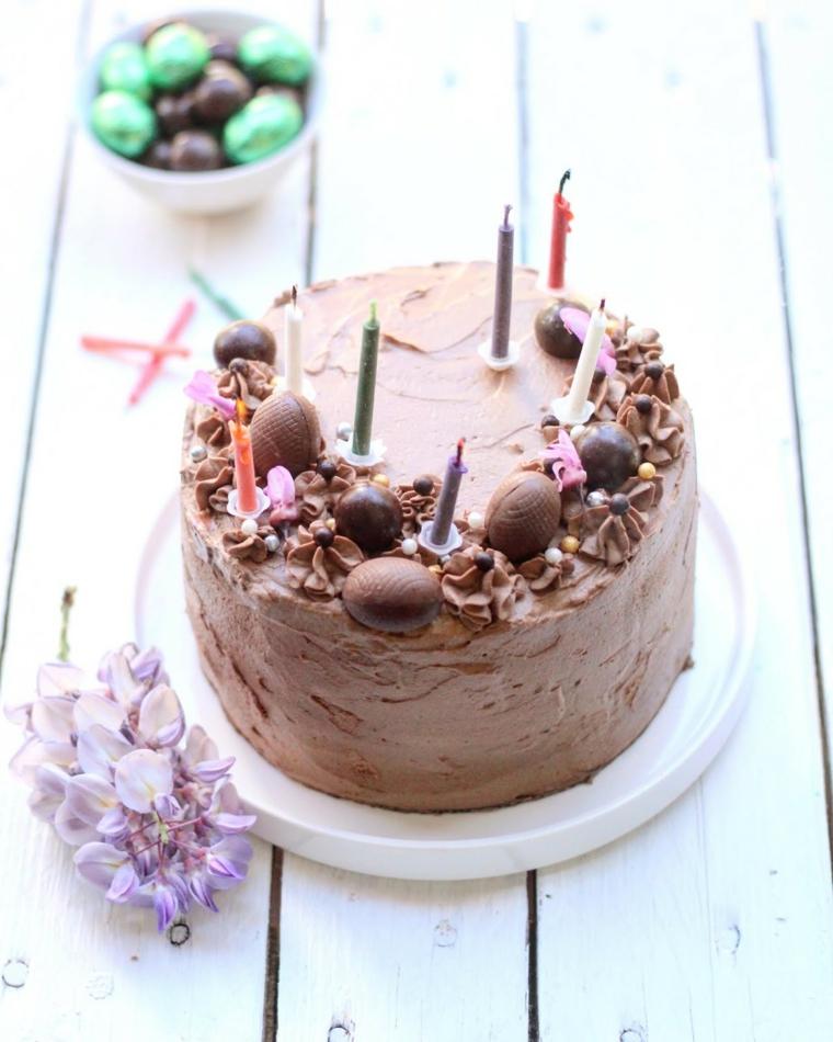 Torta al cioccolato, decorazioni con cioccolatini, candeline colorate, tavolo di legno