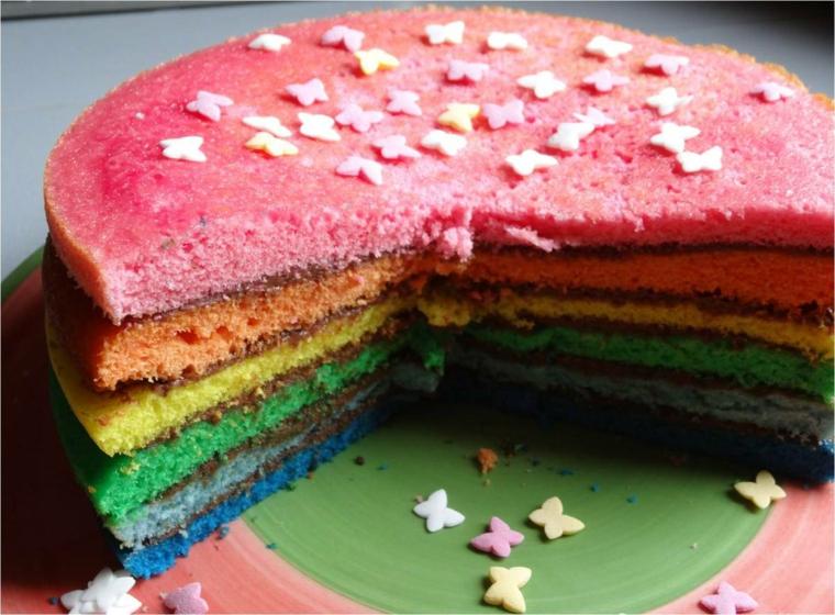 Dolce a strati colorati, decorazioni con farfalle di zucchero, torta rotonda tagliata