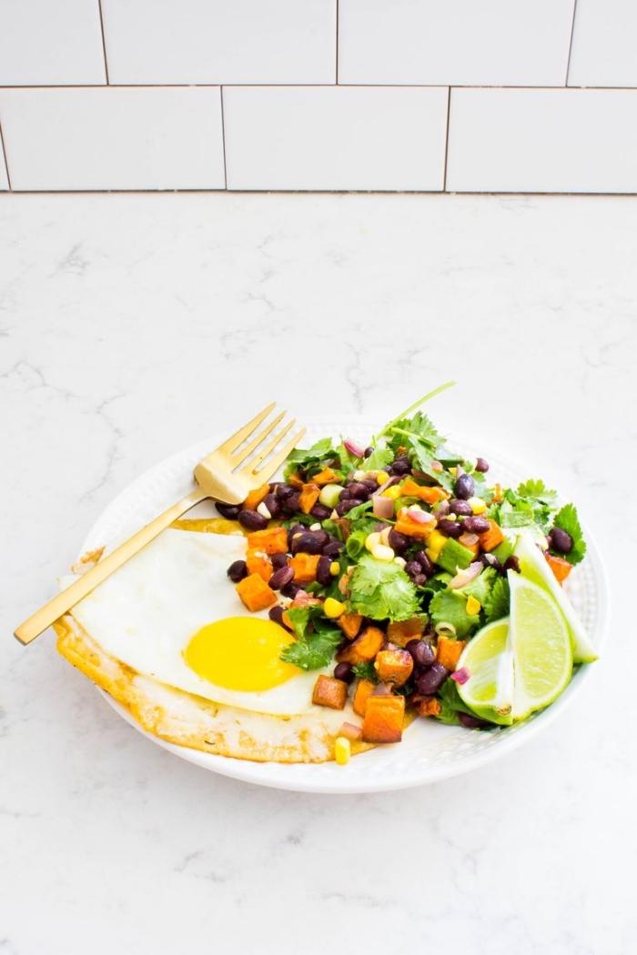 Uova all'occhio di bue, contorno con insalata di fagioli e lattuga, fette di limone per condimento