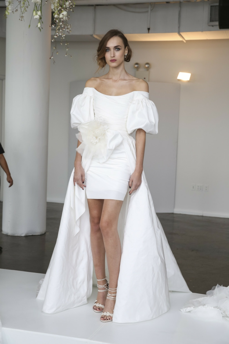 Vestito corto con strascico, maniche vestito voluminosi, capelli sposa raccolti