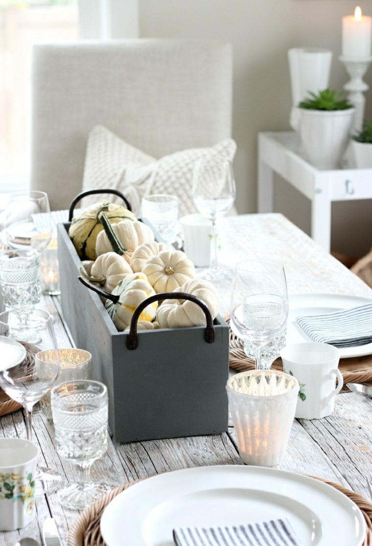 Centrotavola con zucche, cassetta di legno, tavola apparecchiata, piatti e posate