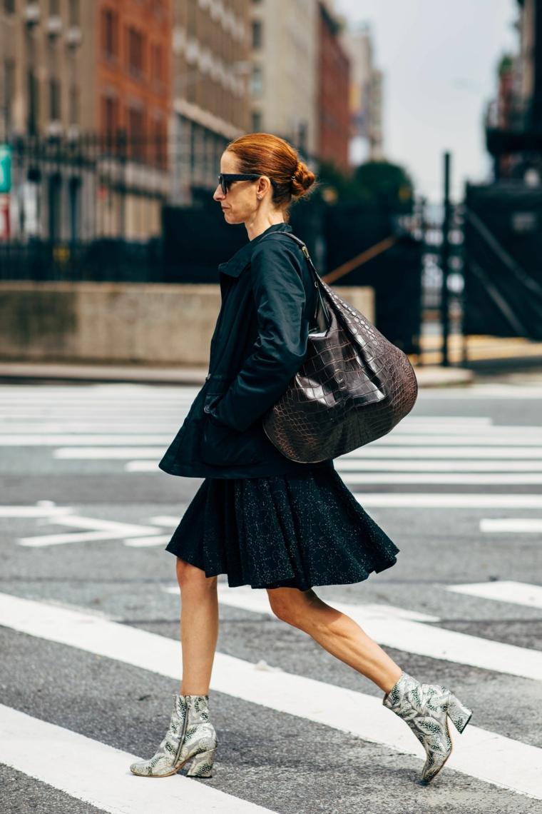 Moda autunno inverno 2019, donna che cammina, gonna plissettata nera, acconciatura capelli chignon