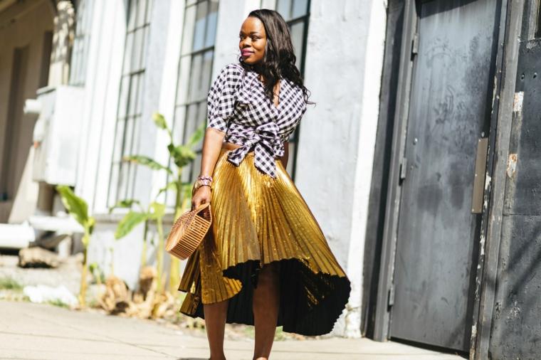 Gonna plissettata colore oro, donna con capelli ricci, camicia con nodo a quadretti