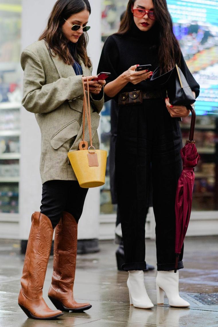 Tendenze autunno inverno 2019, due ragazze che guardano il telefono, stivali marroni da cowboy