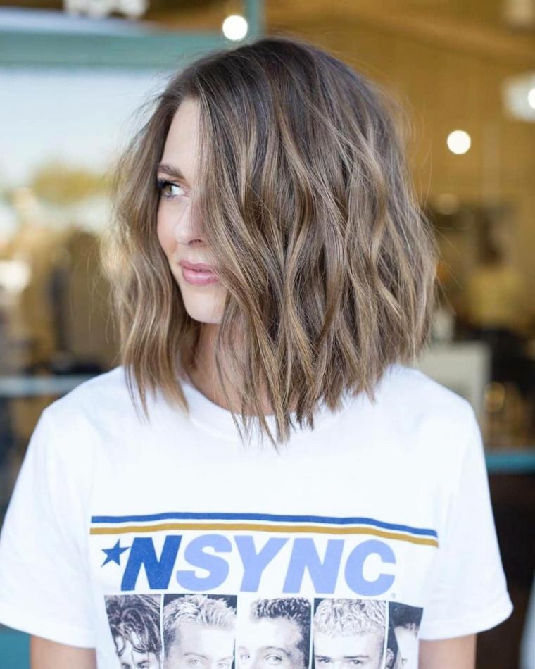 Tagli capelli ricci corti dietro e lunghi davanti, colorazione capelli biondo balayage, pettinatura onde morbide
