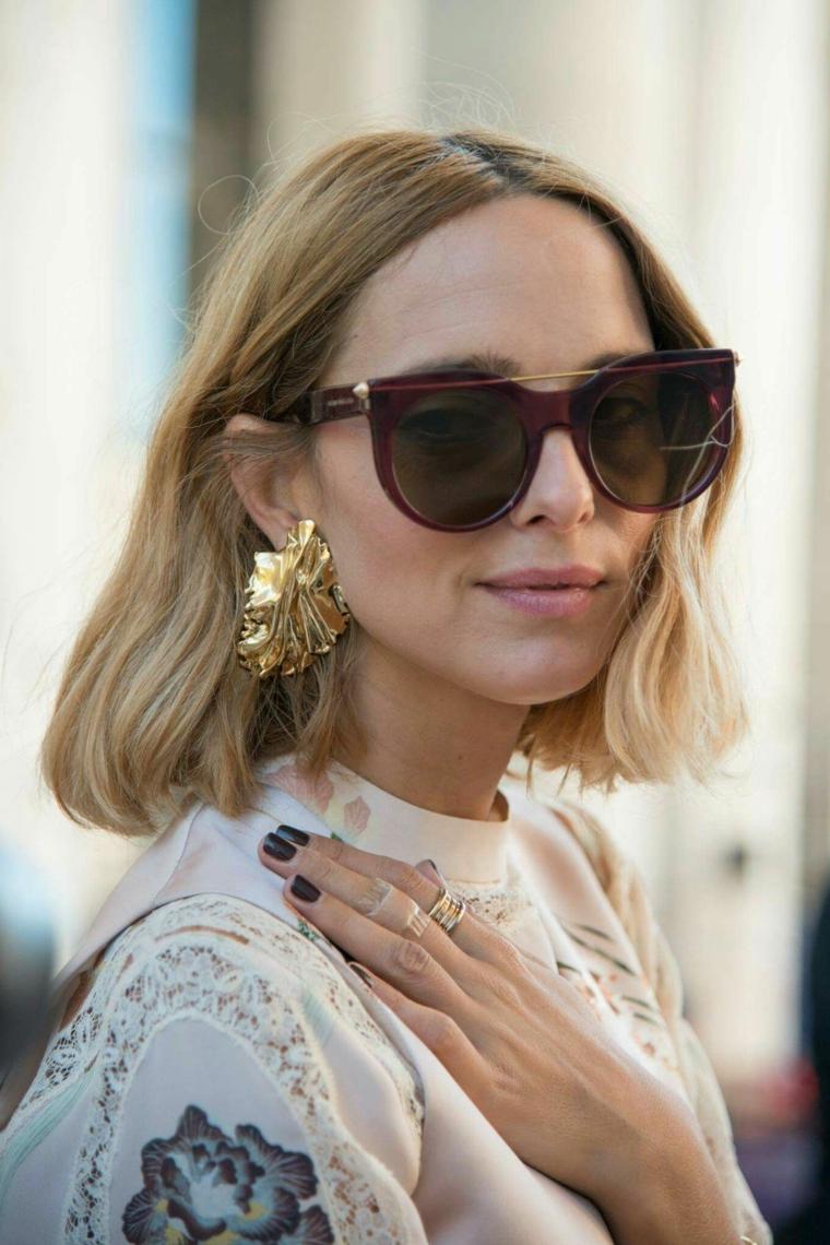 Taglio corto capelli ricci, donna con occhiali da sole, capelli biondi mossi, orecchini colore oro