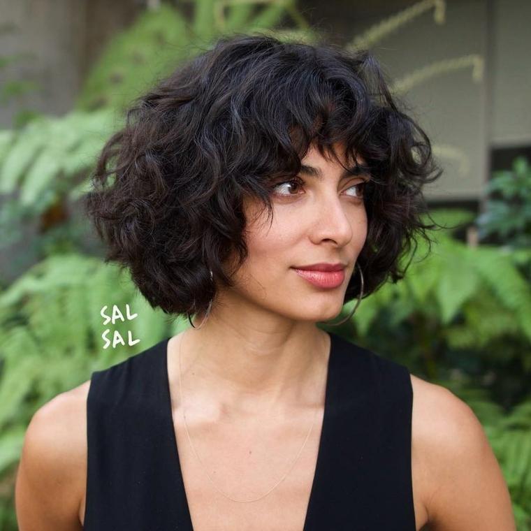 Taglio corto capelli ricci, ragazza con capelli neri, pettinatura con frangia riccia, viso di profilo di una donna