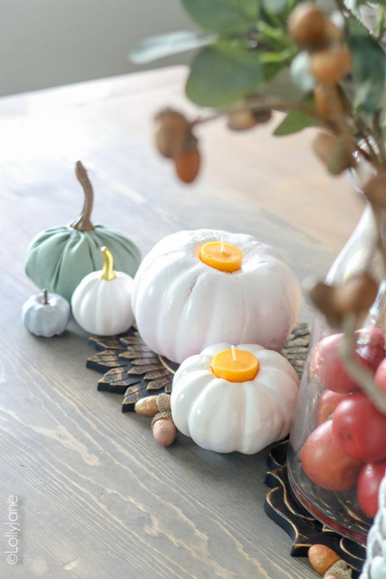 Immagini foglie autunnali, zucche e candele, portacandele forma zucca, tavola di legno