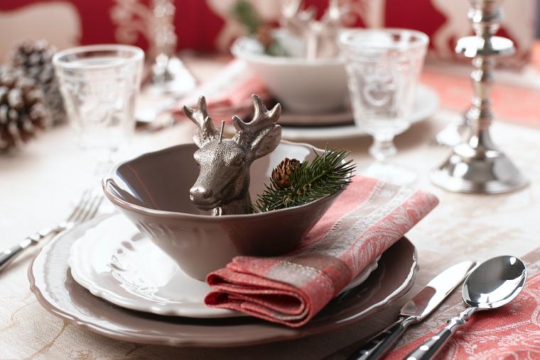 Segnaposto con statuina di renna, pigna e rametto, tavola apparecchiata, decori natalizi