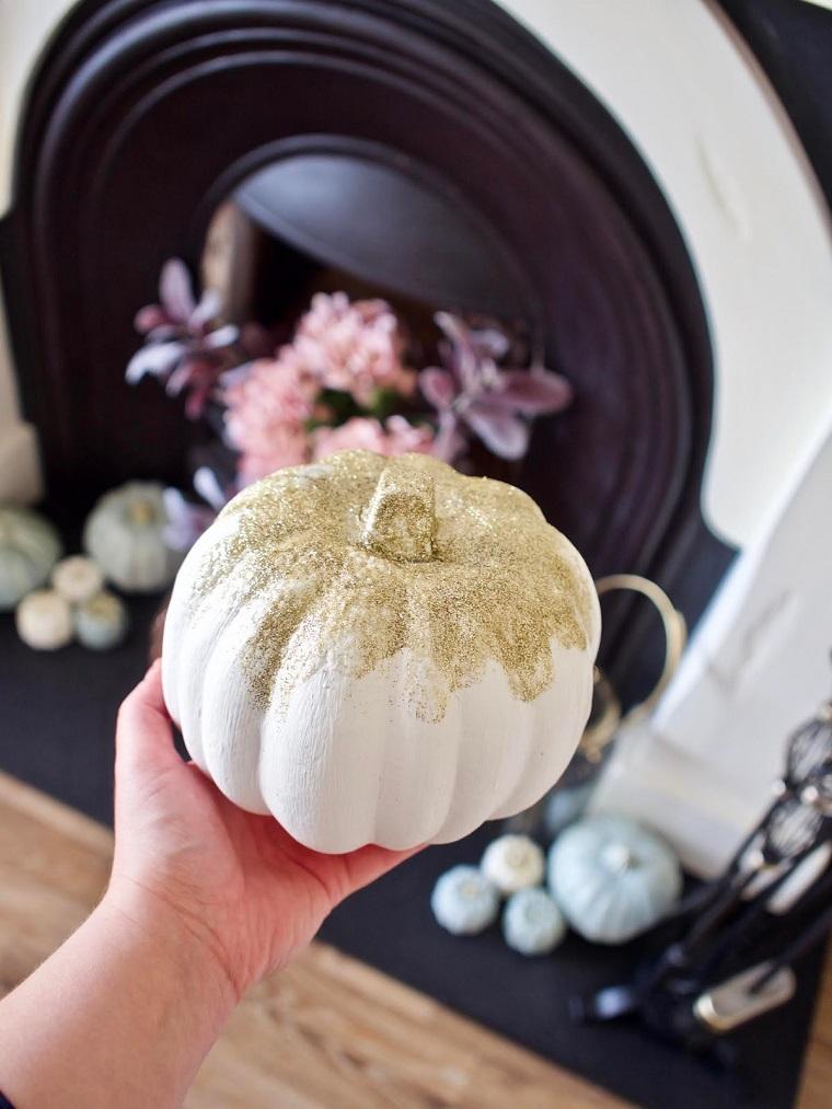 Zucca con glitter oro, zucca dipinta di bianco, addobbi di Halloween, soggiorno con camino