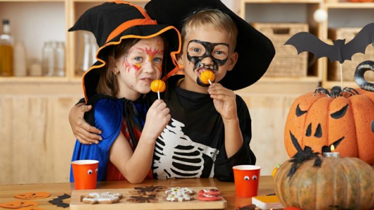 Due bimbi truccati per Halloween, lecca lecca forma di zucca, dolcetti di Halloween