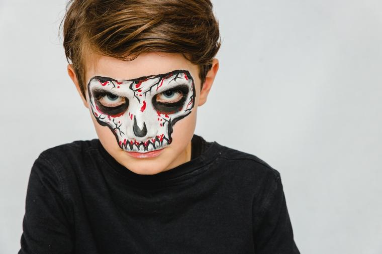 Trucco scheletro halloween, bimbo truccato, disegno sul viso, ragazzo con riga laterale