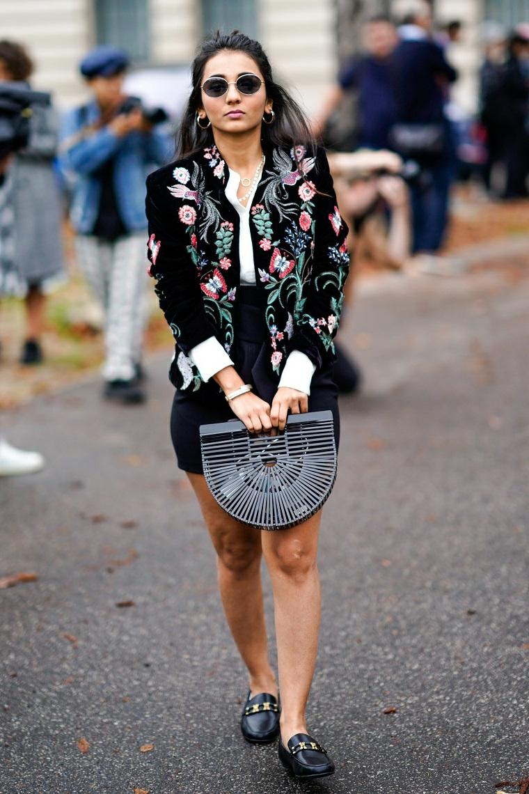 Donna che cammina in strada, giacca nera con ricamo, borsetta piccola in mano, tendenze autunno inverno 2019