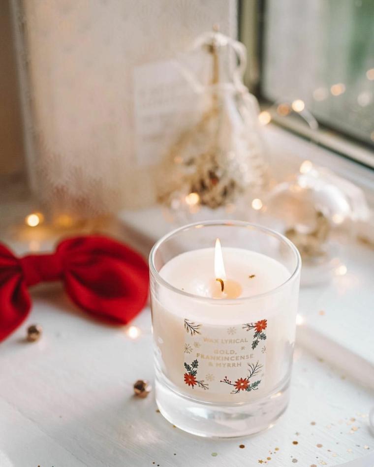 Composizioni natalizie, candela di vetro, fiocco di colore rosso, filo con lucine