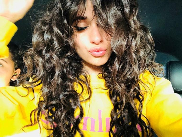 Acconciature capelli ricci, pettinatura con frangia, ragazza con capelli lunghi mossi