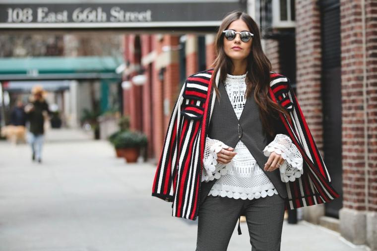 Donna con giacca colorata, capelli castani mossi, camicia bianca a rete