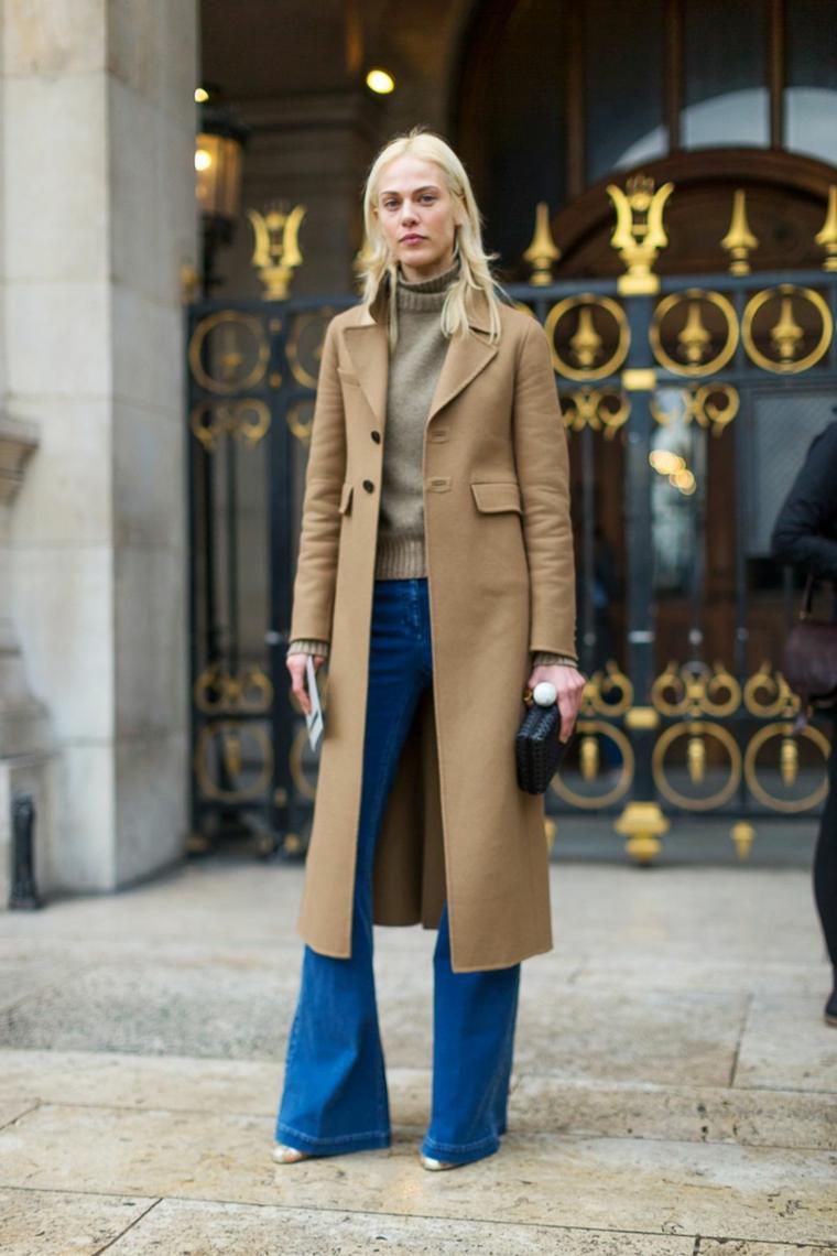 Donna con capelli biondi, cappotto colore marrone, jeans a zampa larga
