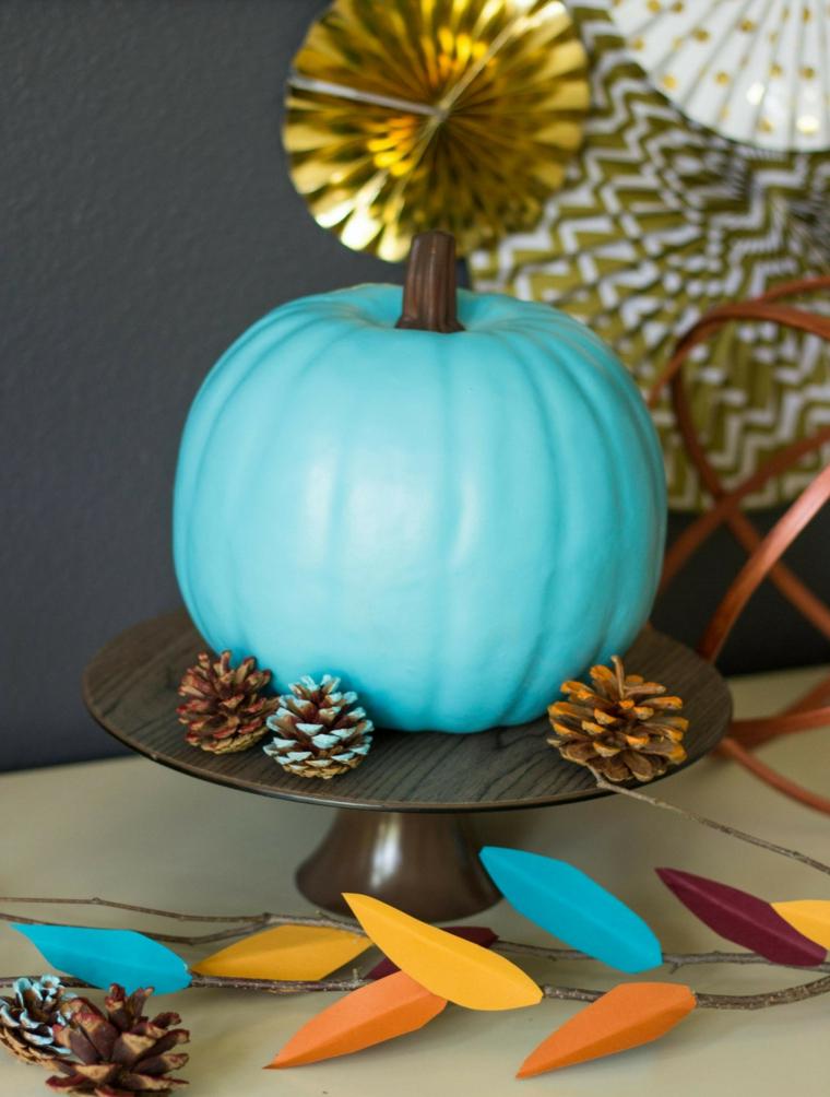 Zucca finta dipinta di blu, rametto con foglie finte, composizioni autunnali, pigne colorate