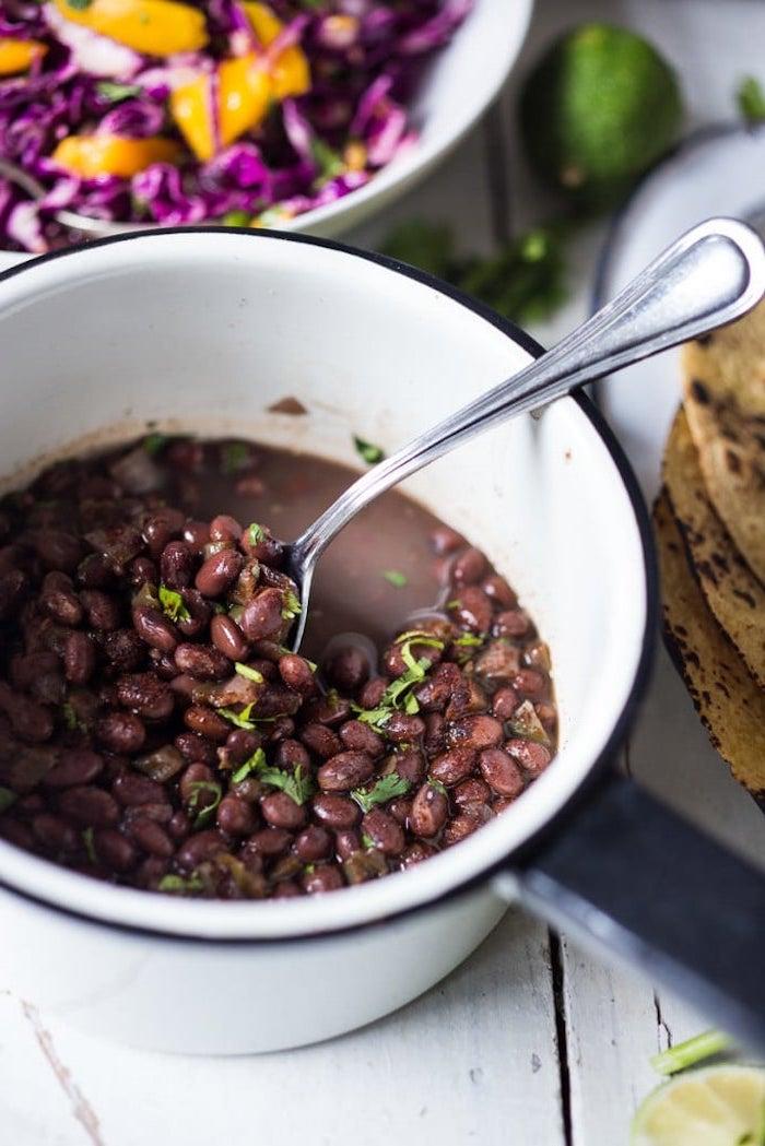 Ciotola con fagioli neri, cucchiaio con fagioli, cena tipica messicana, ingredienti sul tavolo