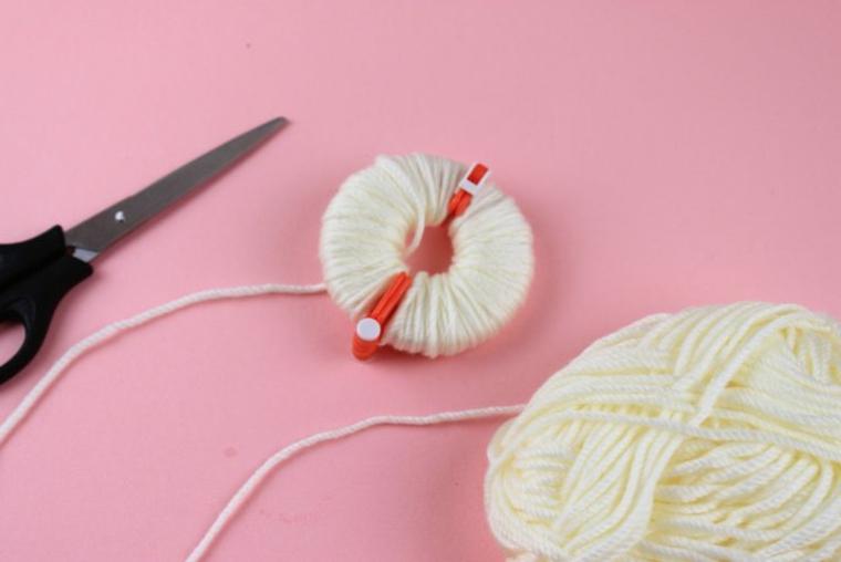 Rotolo di lana, filo di lana bianco, forbici e aggeggio per pom pom, decori natalizi