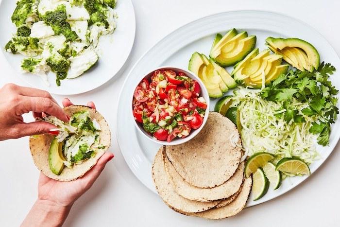 Cosa mettere nelle tortillas, tacos con fettine di avocado, piatto con verdure tagliate
