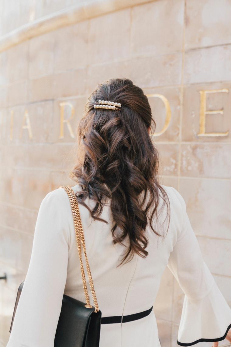 Acconciature capelli ricci, due mollette con perle, pettinatura con boccoli, donna girata di spalle