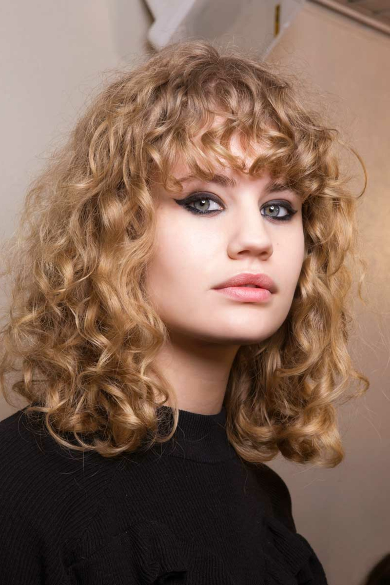 Taglio capelli long bob, capelli di colore biondo, capelli con frangia, pettinatura chioma riccia