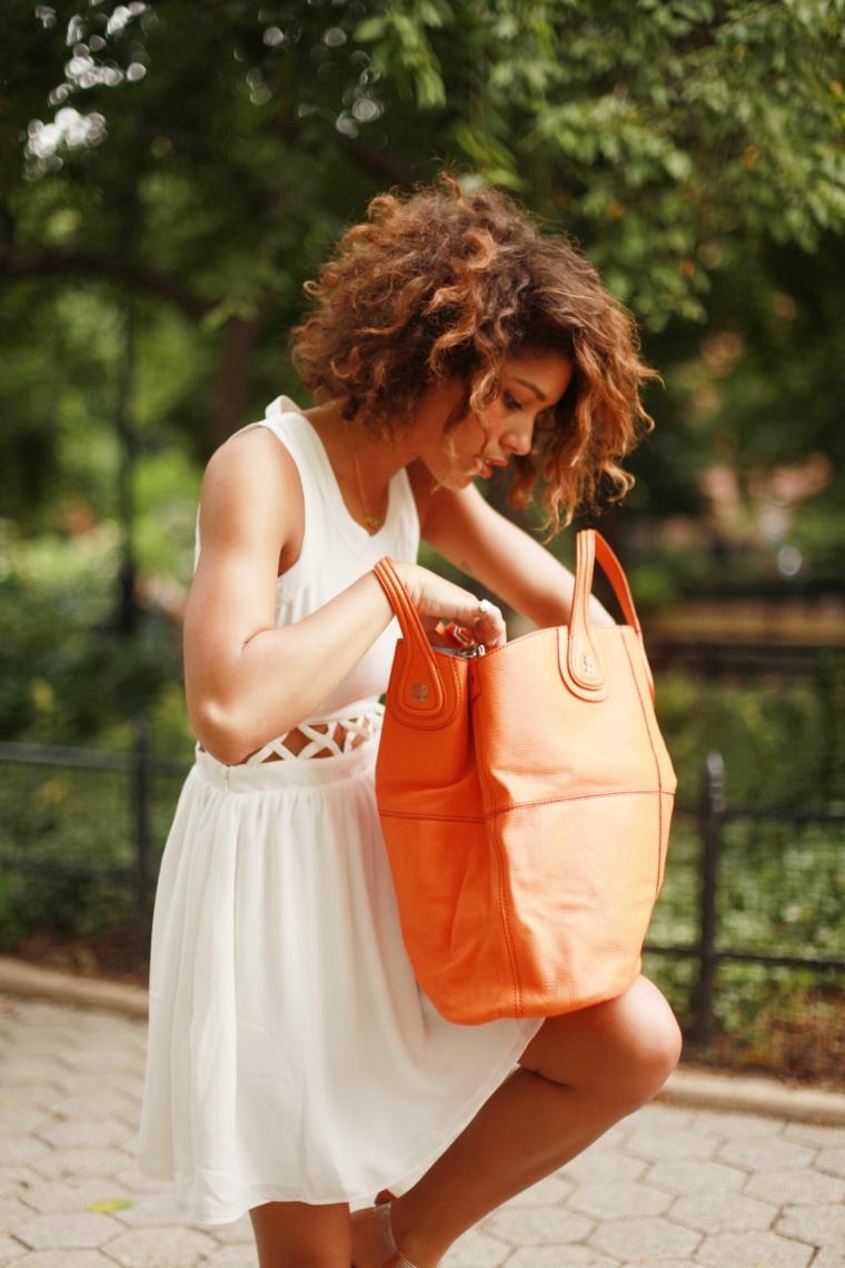 Ragazza che cerca nella borsa, capelli taglio caschetto, pettinature capelli ricci, borsa di pelle arancione