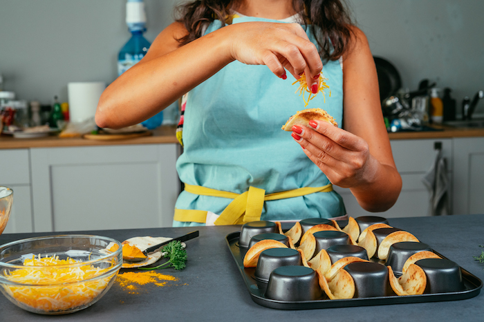 Piatti messicani, tacos con ripieno, formaggio grattugiato, donna che cucina