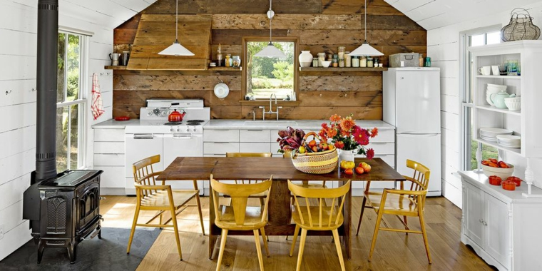 Cucina con tavolo, composizioni autunnali, camino a legna, cucina rustica