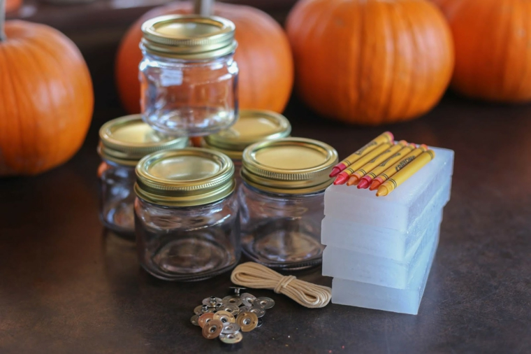 Materiali per fare una candela, barattoli di vetro, pastelli di cera colorati, zucche arancioni
