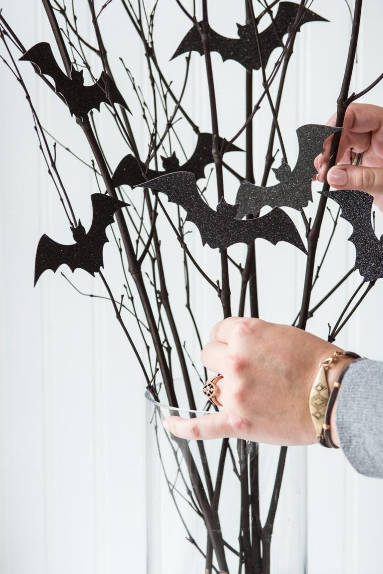 Vaso con rametti, pipistrelli di carta, decorazioni semplici per Halloween, mani di una donna