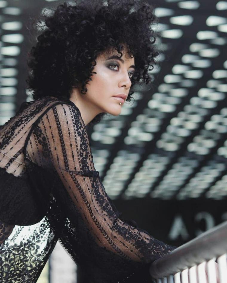 Capelli ricci donna, pettinatura con frangia, capelli neri ricci, camicia nera trasparente
