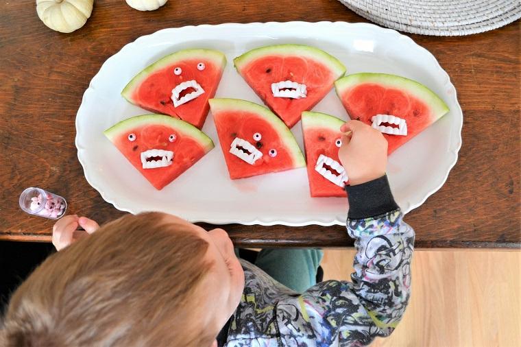 Piatto con pezzi di anguria, bambino che mangia anguria, pezzi di anguria con denti di caramelle