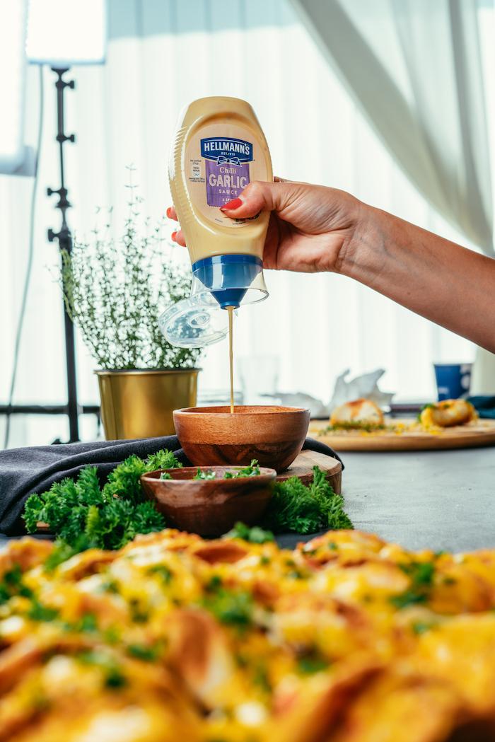 Tortillas ripieno, ciotola con maionese, donna che versa la maionese, tortillas con formaggio fuso