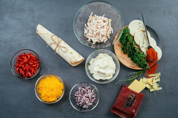 Come si preparano le tortillas messicane, ciotole con peperoni, formaggio cheddar grattugiato, pezzettini di pollo