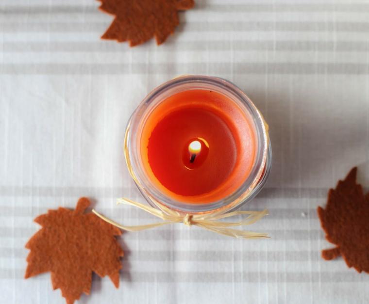 Immagini foglie autunnali, candela di colore arancione, candela fai da te con fiamma