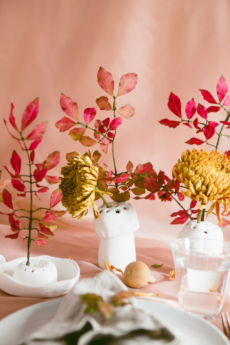Centrotavola con vasi, rametti in vasi, tavola apparecchiata, foglie autunnali