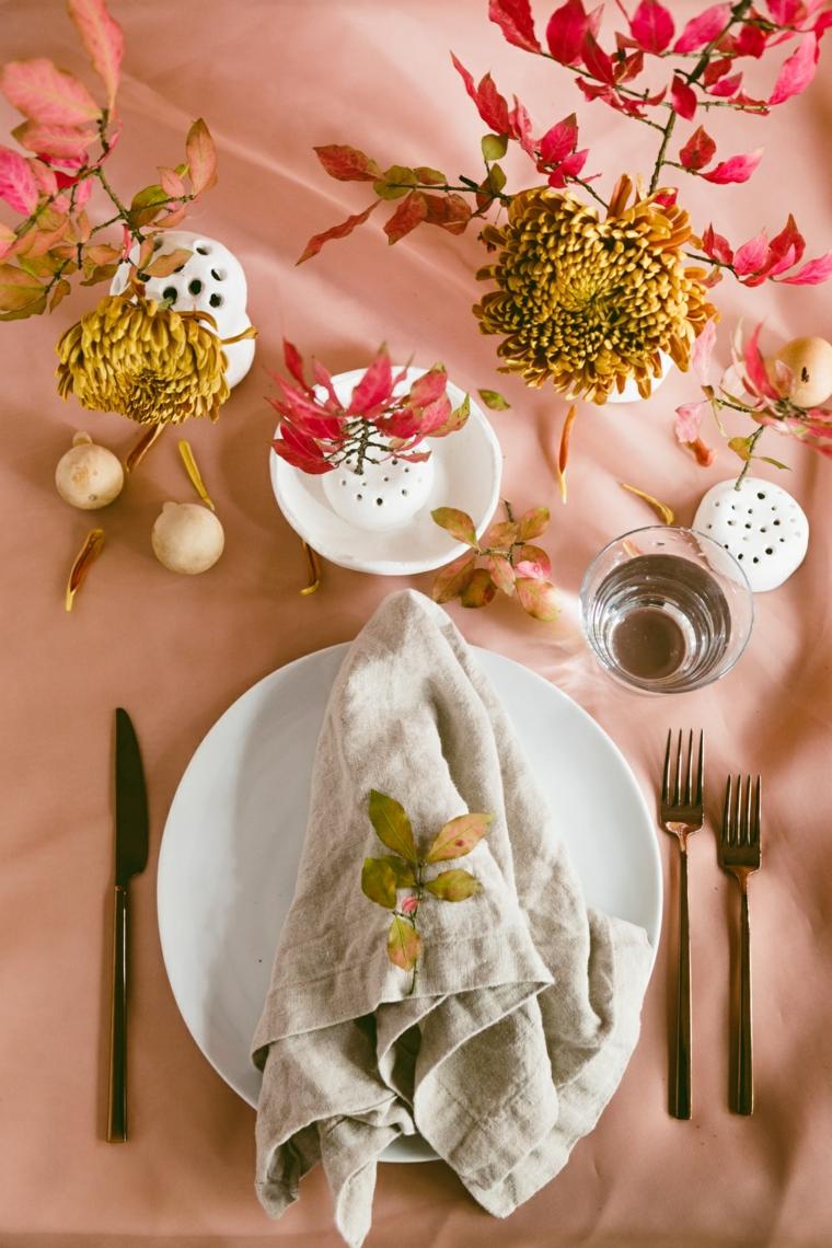 Segnaposto con foglie, vasi di fiori, rametti con foglie, tavola apparecchiata, piatti e posate