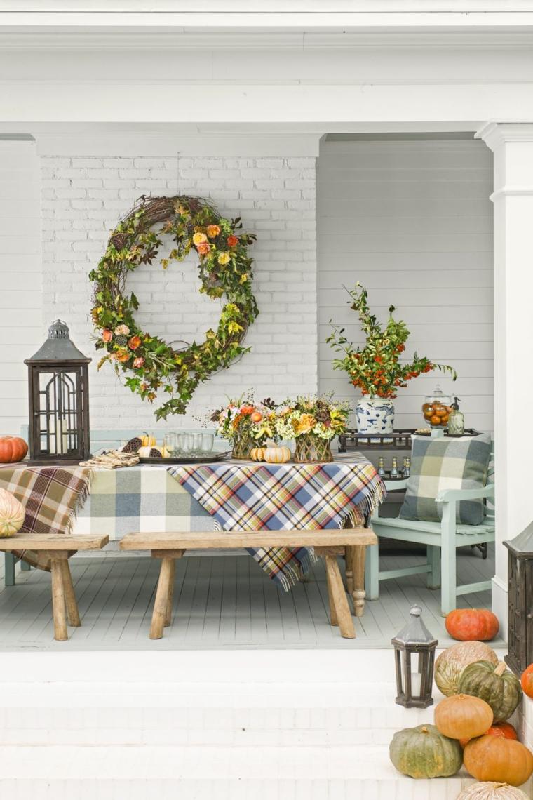 Ghirlanda con rametti verdi, addobbi con zucche, tavola di legno e panchina