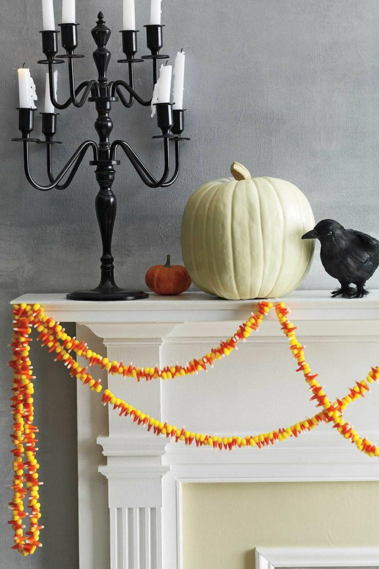 Camino decorato con zucche, candelabro con candele, ghirlanda con caramelle di Halloween