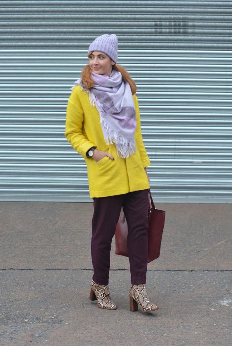 Tendenze autunno inverno 2019, giacca di colore giallo, stivali snakeskin, capello di lana grigio