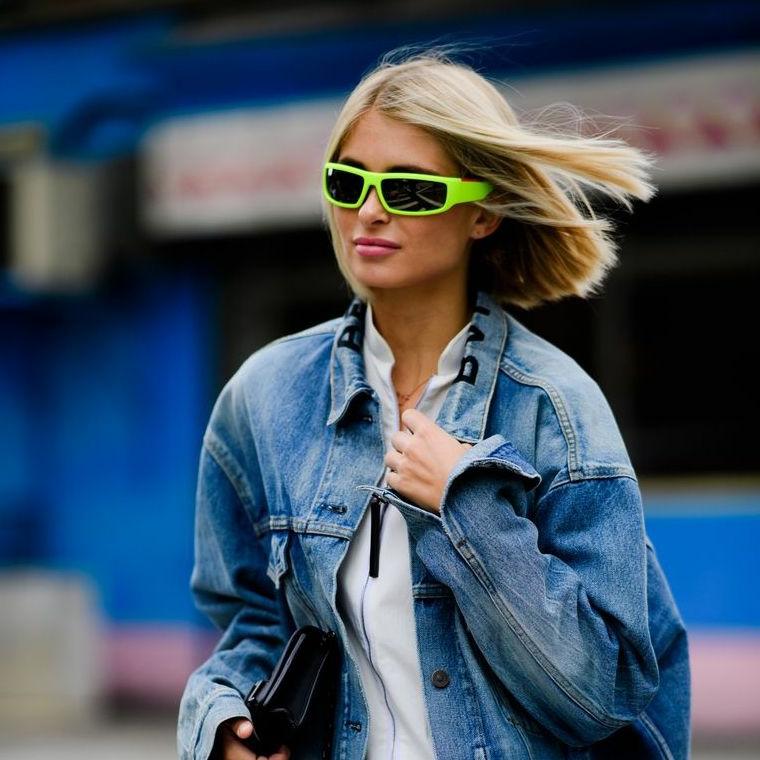 Outfit inverno 2019, donna con occhiali da sole verdi, capelli biondi corti, giacca in jeans