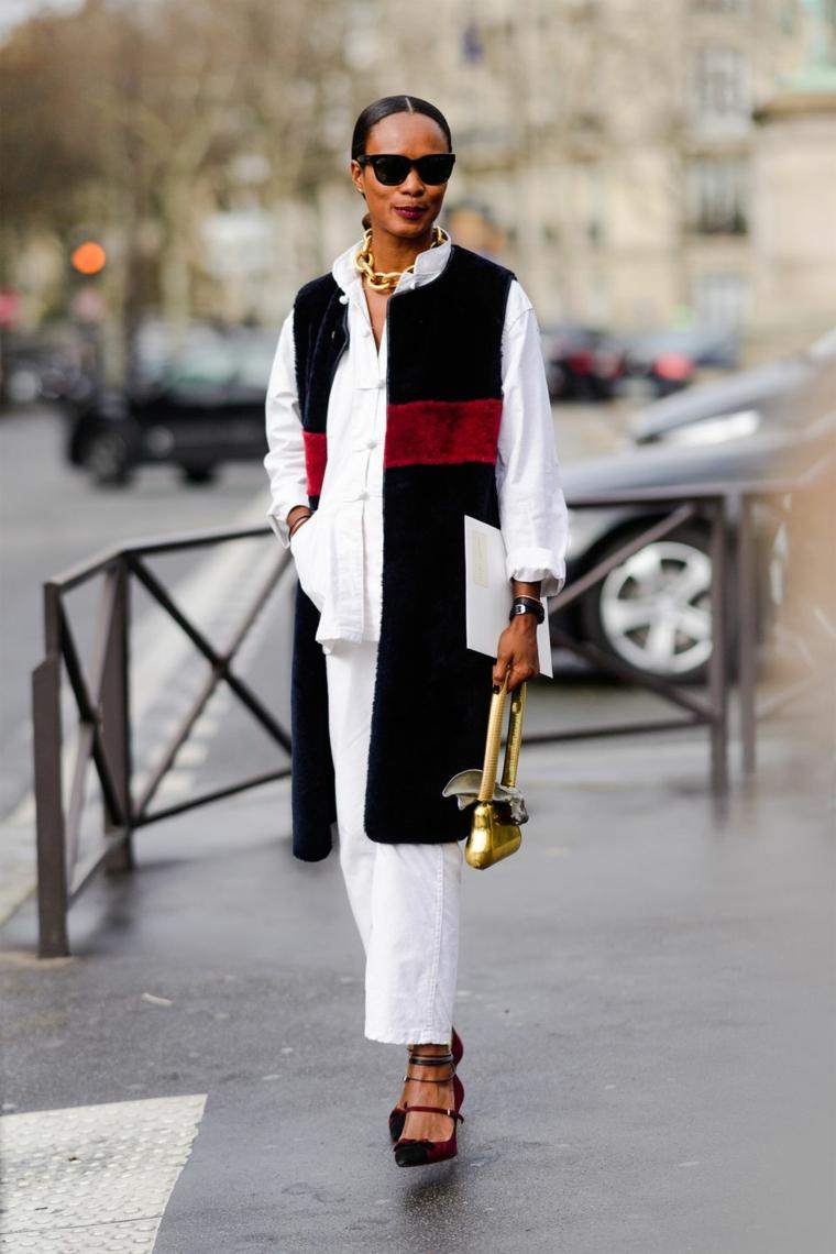 Colori moda inverno 2019, donna che cammina, pantalone jeans bianco, collana a catena grossa