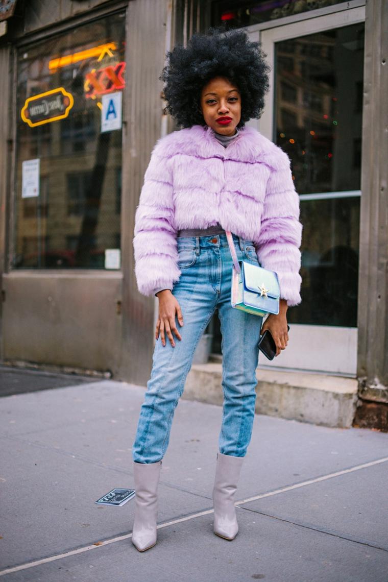Ragazza con capelli ricci, giacca pelliccia viola, jeans a vita alta, borsetta a tracolla