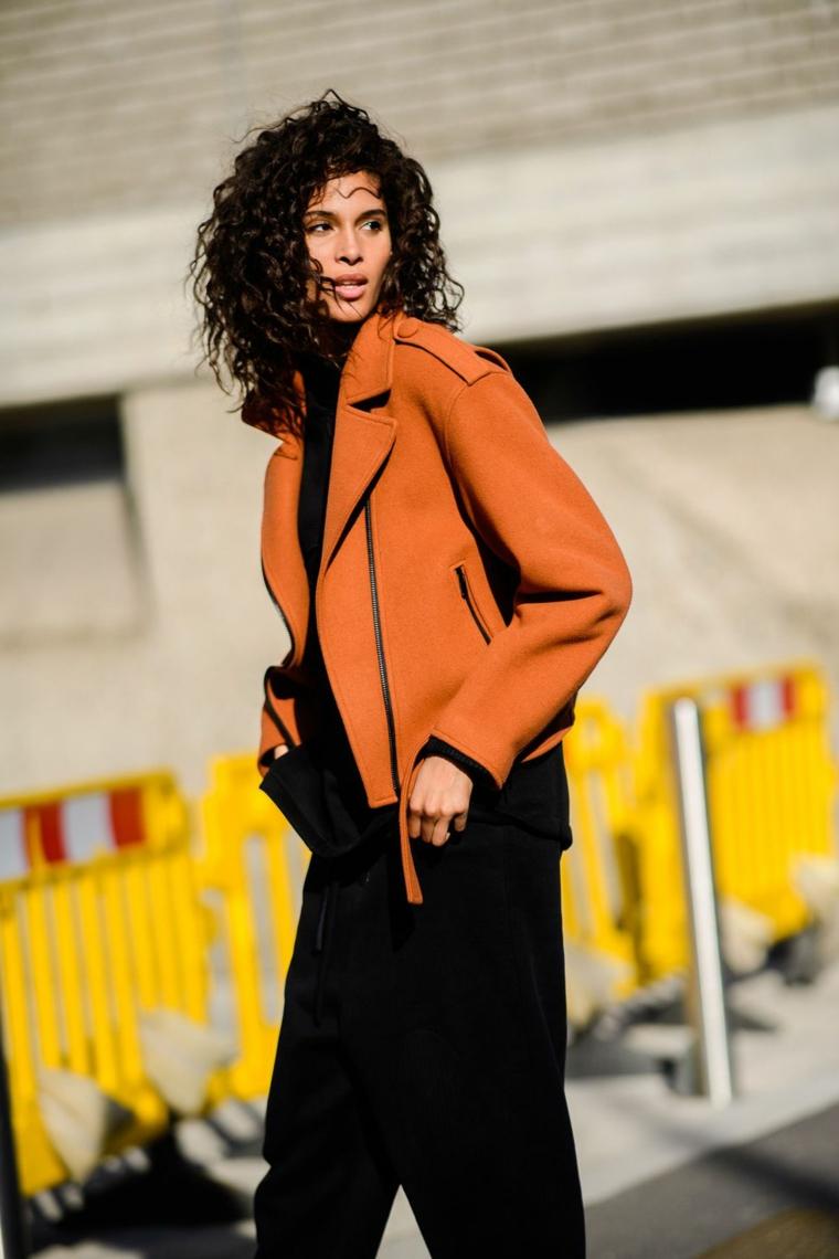 Donna con capelli ricci, giacca di colore marrone, pantalone nero largo