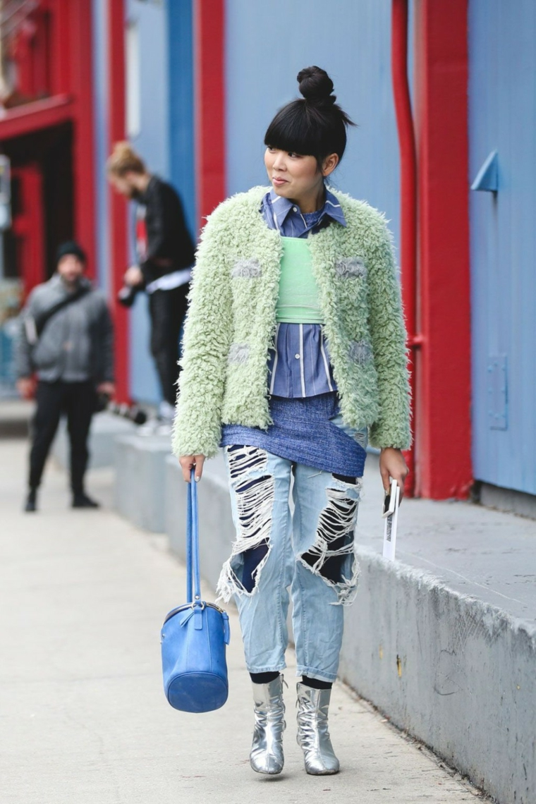 Ragazza che cammina per strada, capelli legati a chignon, giacca verde pelliccia, jeans con strappi davanti