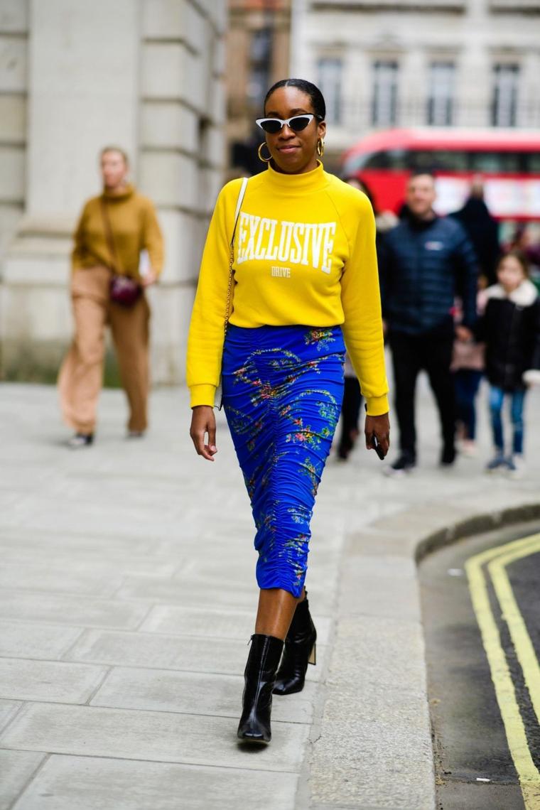 Donna che cammina, gonna tubino colorata, felpa gialla con scritta, stivaletti neri caviglia