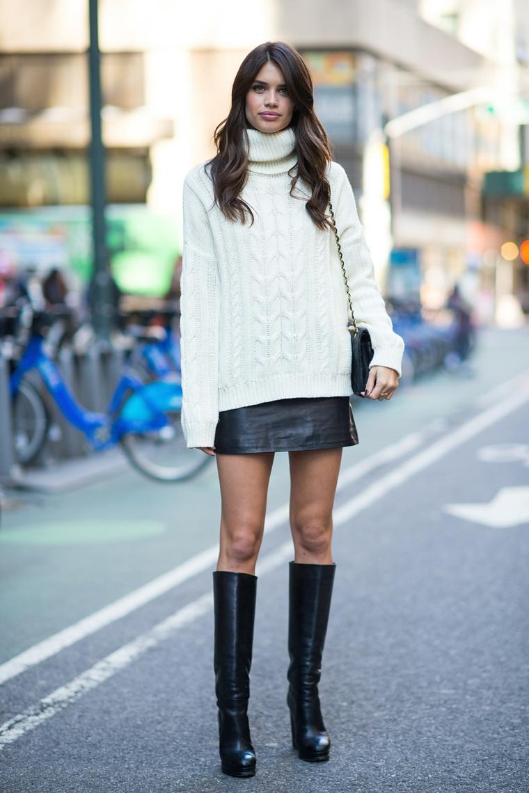 Ragazza che cammina per strada, stivali alti neri, maglione di lana bianco, moda autunno inverno 2019